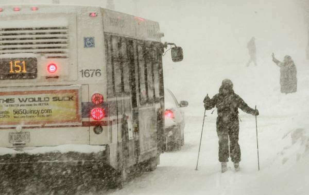 A city bus passes a skier on Michigan Avenue during a snowstorm in Chicago, Illinois. A blizzard dumped more than 20 inches of snow overnight in Chicago, making it the third largest snowfall recorded in the city's history.