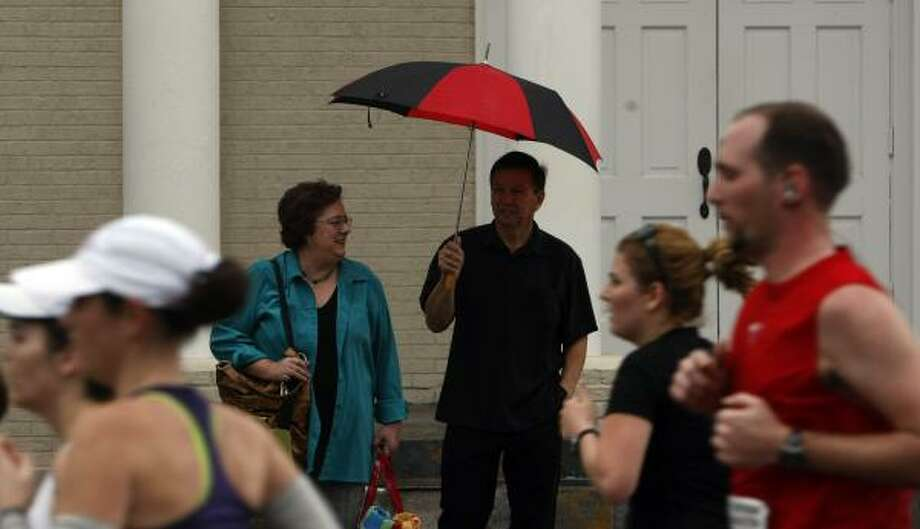 Umbrellas were needed as spectators watched the runners. Photo: Johnny Hanson, Chronicle