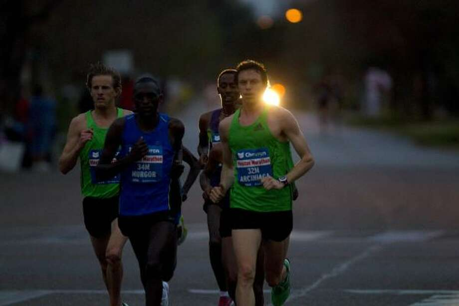A group of elite runners reach the fifth mile ahead of the pack. Photo: Johnny Hanson, Chronicle