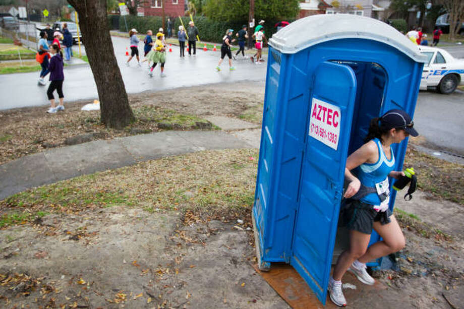 A runner makes a pit stop at as runners pass in the Heights. Photo: Smiley N. Pool, Chronicle