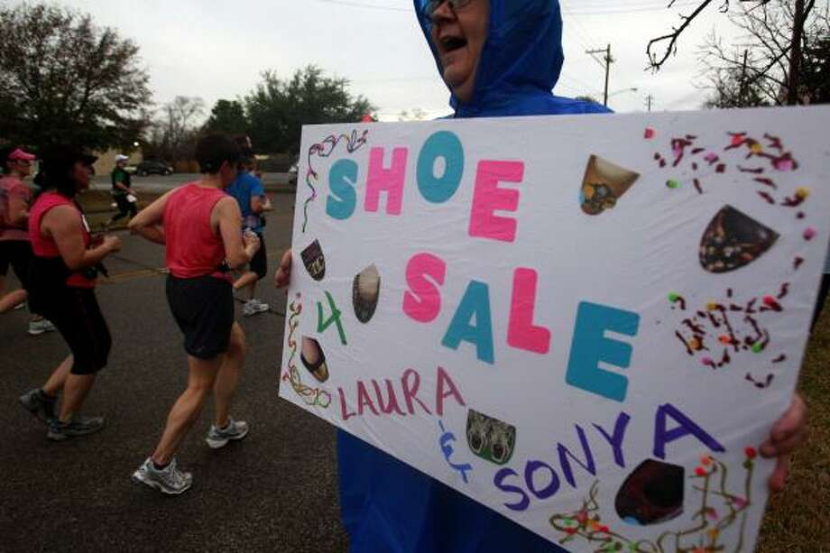 Jackie Woodcki holds a sign to cheer on her friends. Photo: Johnny Hanson, Chronicle