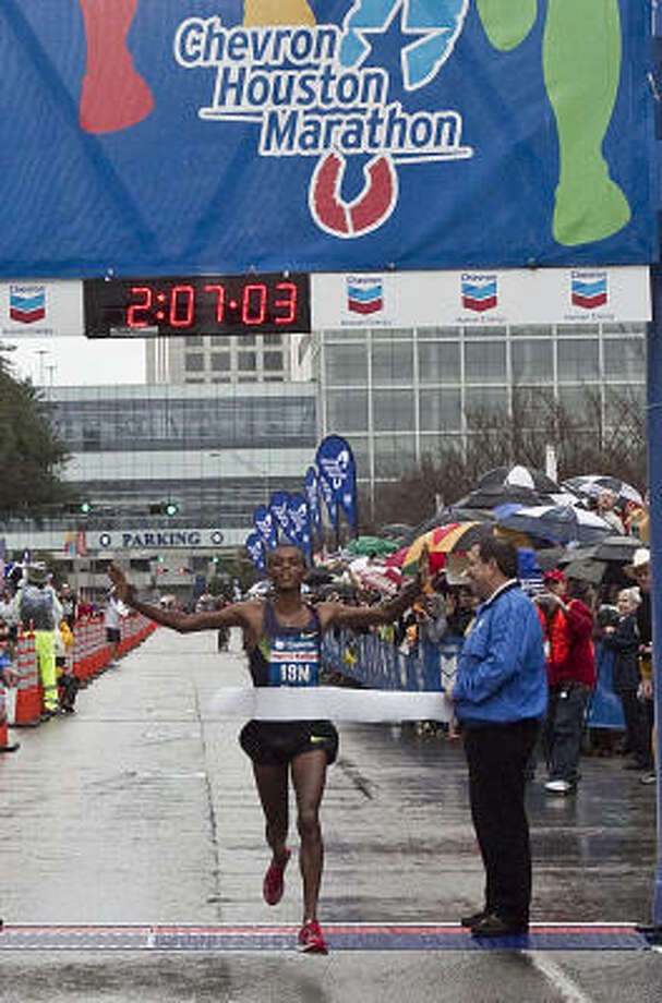 Bekana Daba crosses the finish line to win the men's division. Photo: James Nielsen, Chronicle