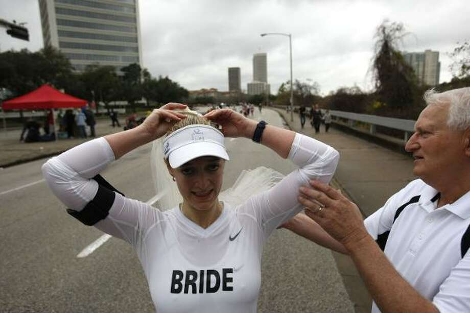 Before getting married, Melissa Manson puts on her veil with the help of her father, Paul Manson, near the 24th mile. Photo: Johnny Hanson, Houston Chronicle
