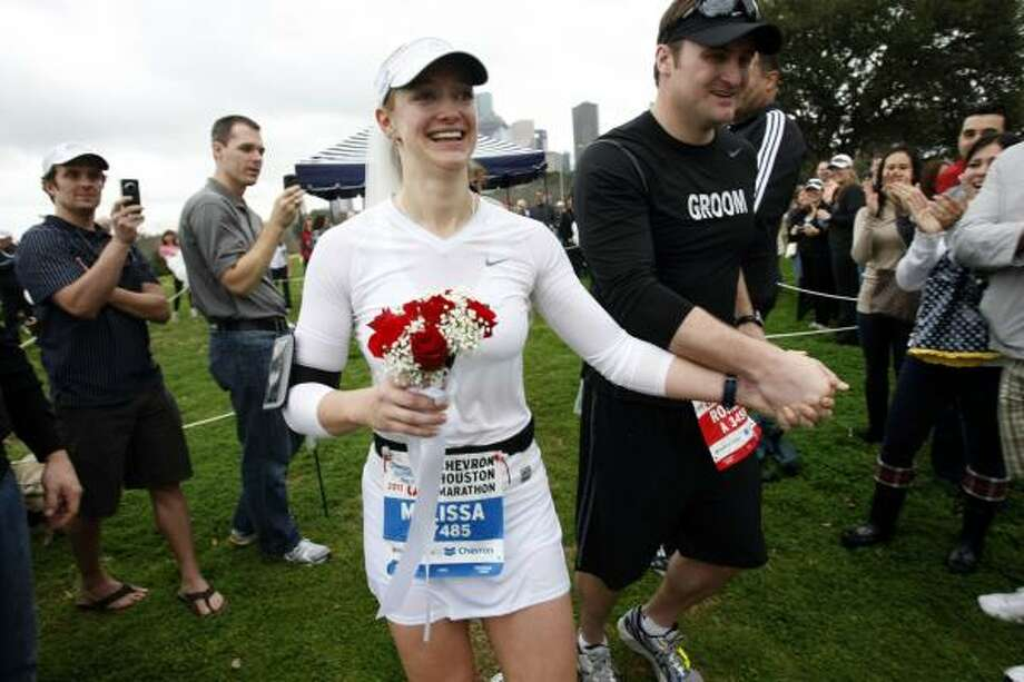 After getting married, Roman Rabourn and his wife Melissa Rabourn (formerly Manson) run back onto Allen Parkway. Photo: Johnny Hanson, Chronicle