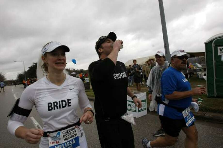 After getting married during a short ceremony near the 24th mile, Roman Rabourn runs with his wife Melissa Rabourn (formerly Manson) as they cover the last few miles. Photo: Johnny Hanson, Chronicle