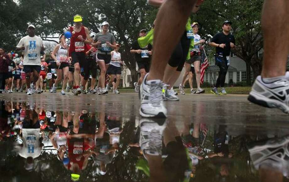 After a short early-morning rain, runners make their way down University Blvd. on the 13th mile. Photo: Johnny Hanson, Houston Chronicle