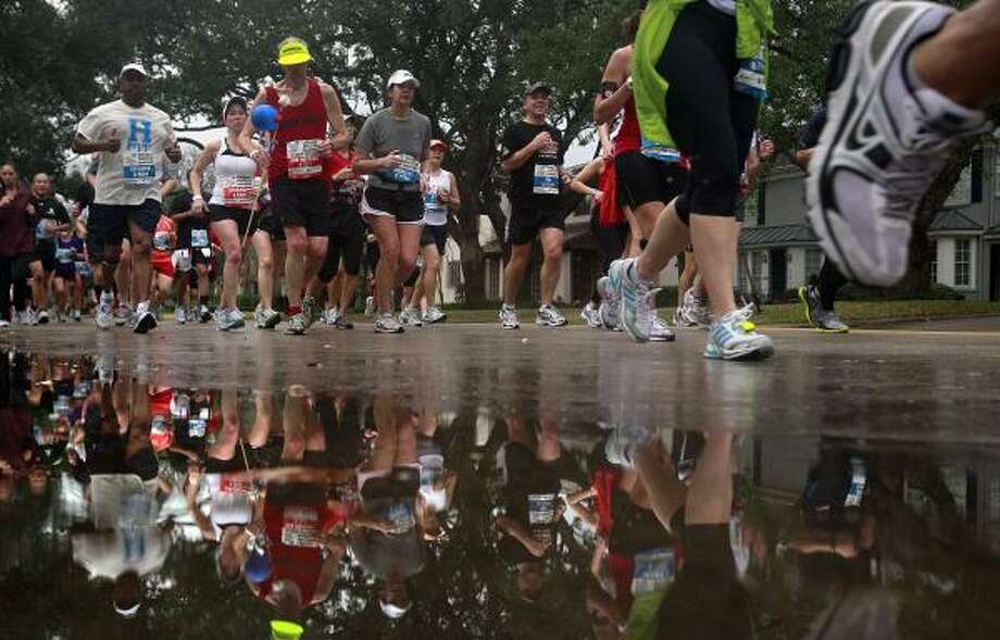 Runners pass pavement with standing water at the 13th mile. Photo: Johnny Hanson, Chronicle