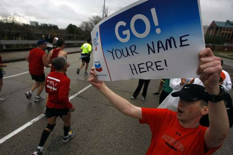 After running the half marathon, Keith Hagler cheers on runners at the 24-mile mark. Photo: Johnny Hanson, Chronicle