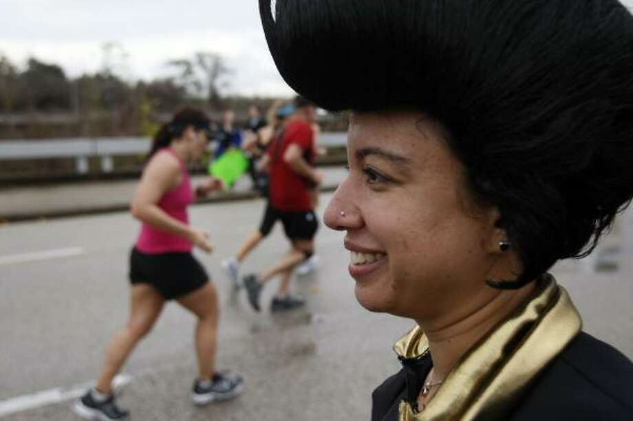 Maya Jaisingh wears an Elvis costume while watching runners run along Allen Parkway on the 24th mile. Photo: Johnny Hanson, Chronicle