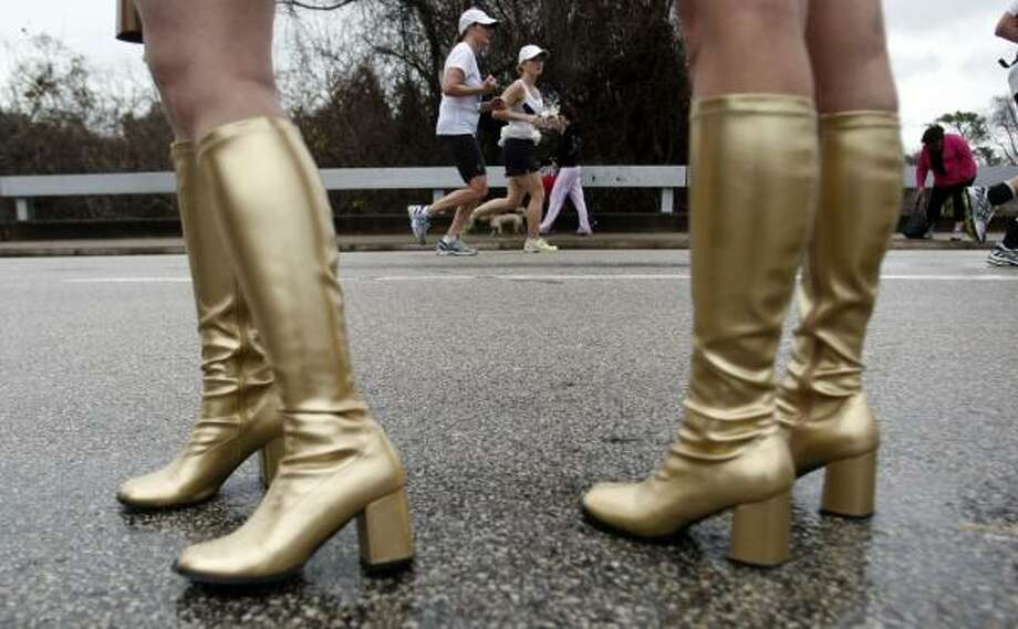 Wearing knee-high boots, Kimberly McCulloch (left) and Kelley Horton cheer on runners along Allen Parkway. Photo: Johnny Hanson, Chronicle