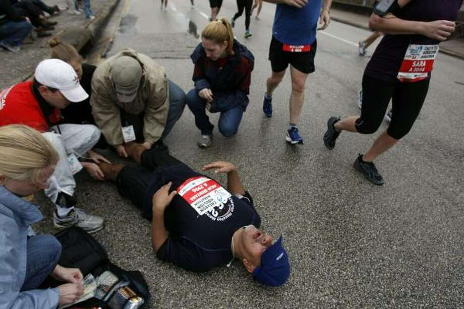 Julio Quintana lies on the pavement while a medical crew works on his cramped legs. Photo: Johnny Hanson, Chronicle