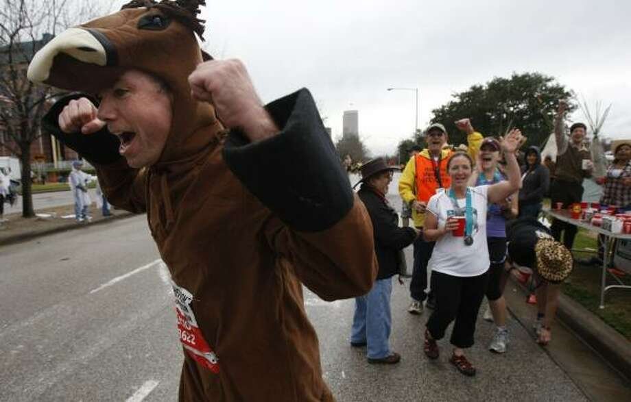 Robert Schamus pumps his fists after putting on a horse costume at the Houston Hash House Harriers runners stop near the 24th mile. Photo: Johnny Hanson, Chronicle