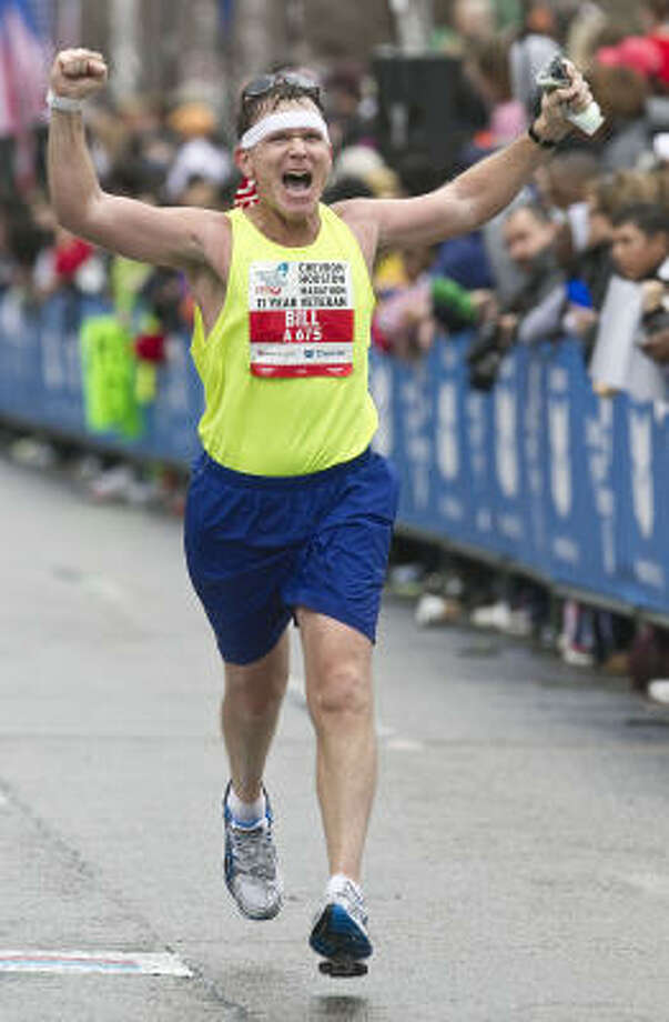 Bill Broderick raises his arms as he approaches the finish line. Photo: James Nielsen, Chronicle
