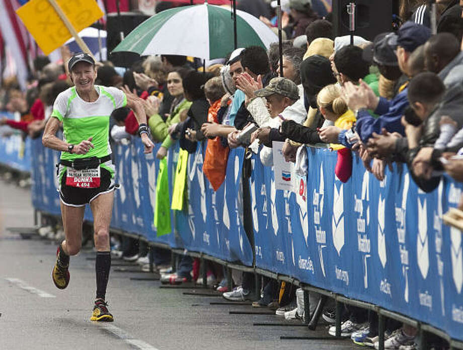 Donna Sterns passes spectators at the end of the marathon. Photo: James Nielsen, Chronicle