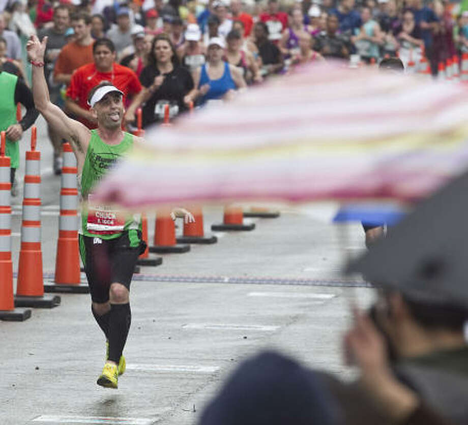 Chuck Roose waves to the crowd on his way to the finish line. Photo: James Nielsen, Chronicle
