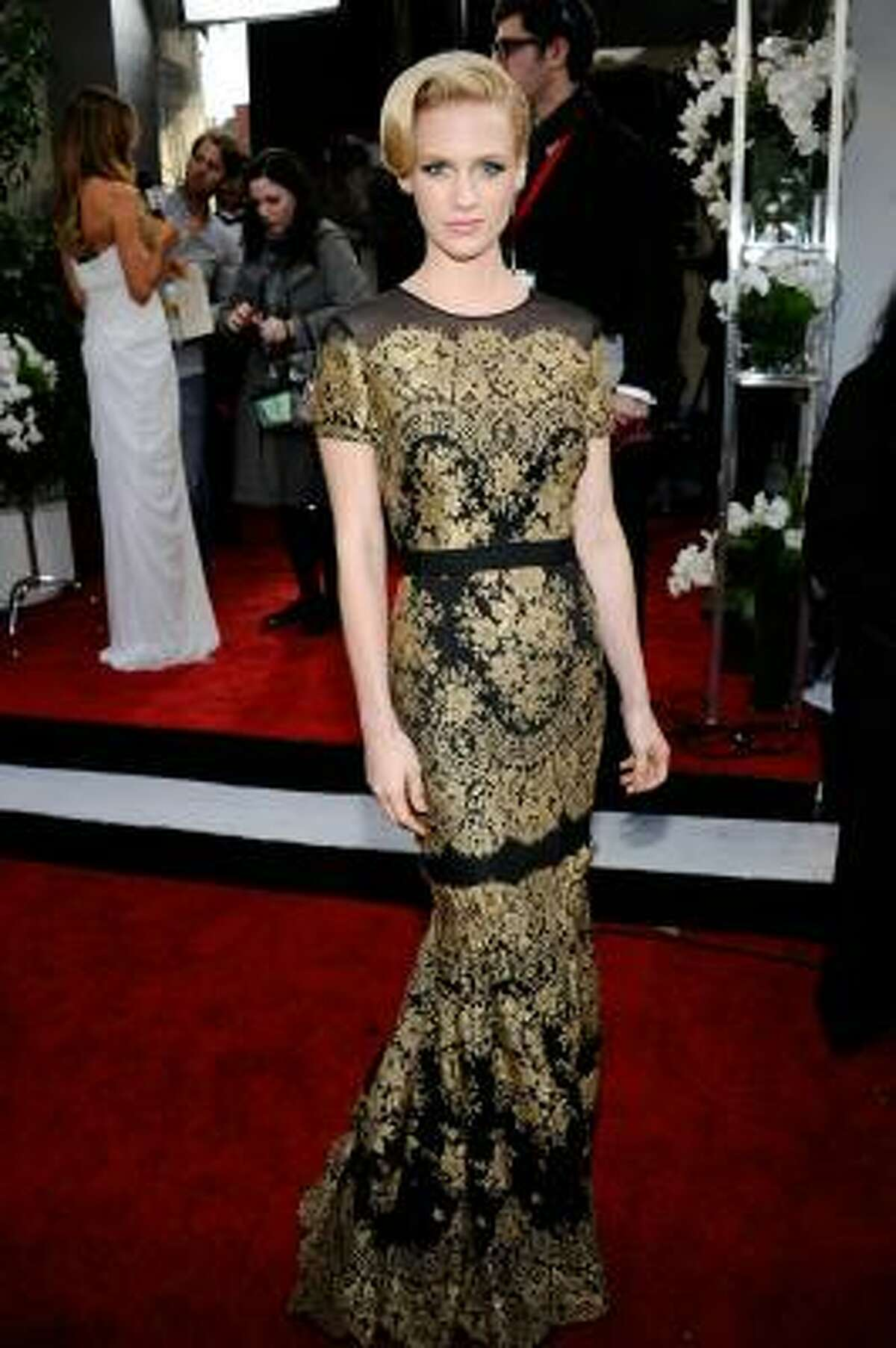 January Jones in a brown and gold lace Carolina Herrera dress with a sophisticated up-do.