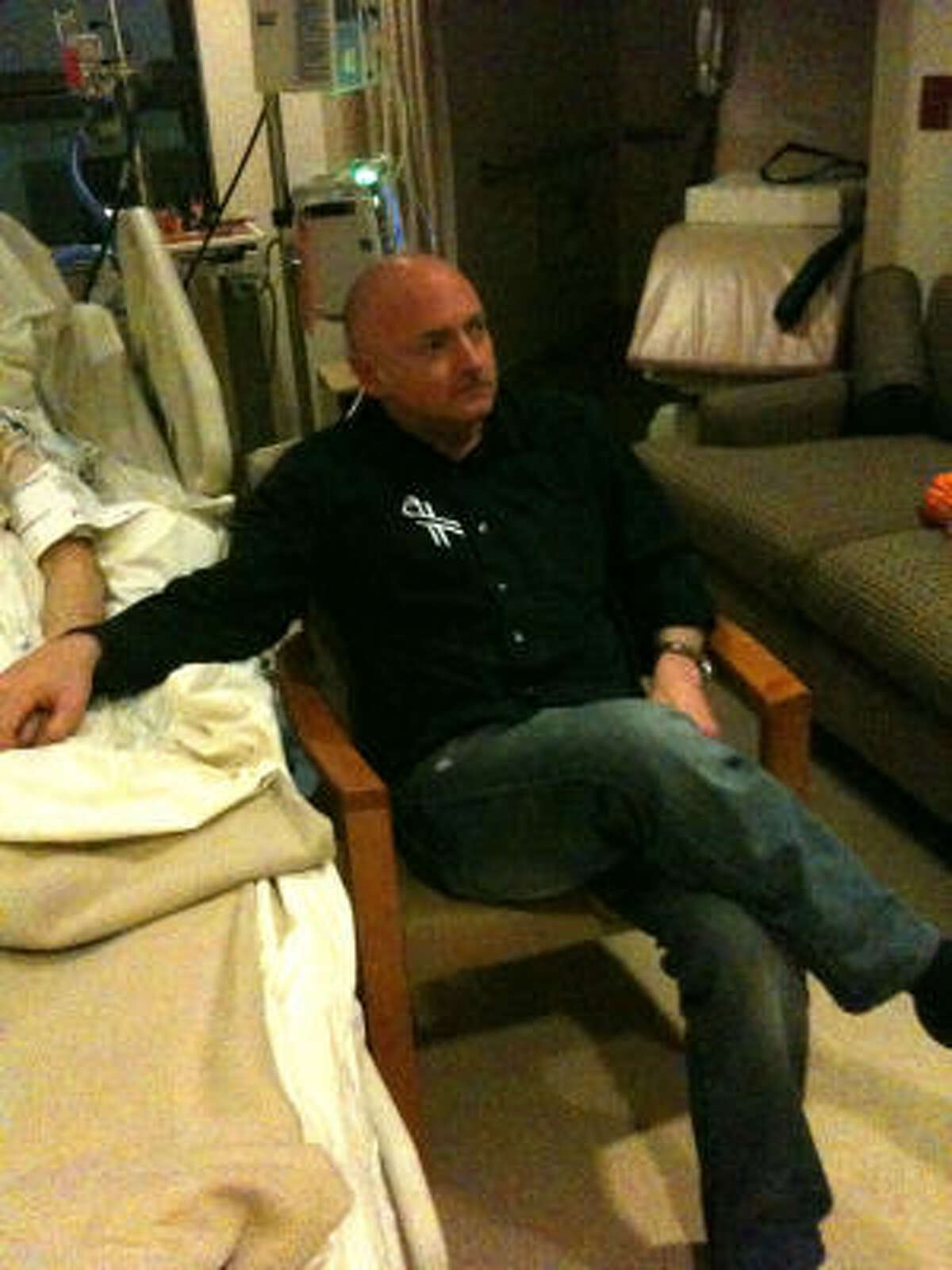 Mark Kelly watches the State of the Union in the hospital room of his wife, Rep. Gabrielle Giffords, in Houston.