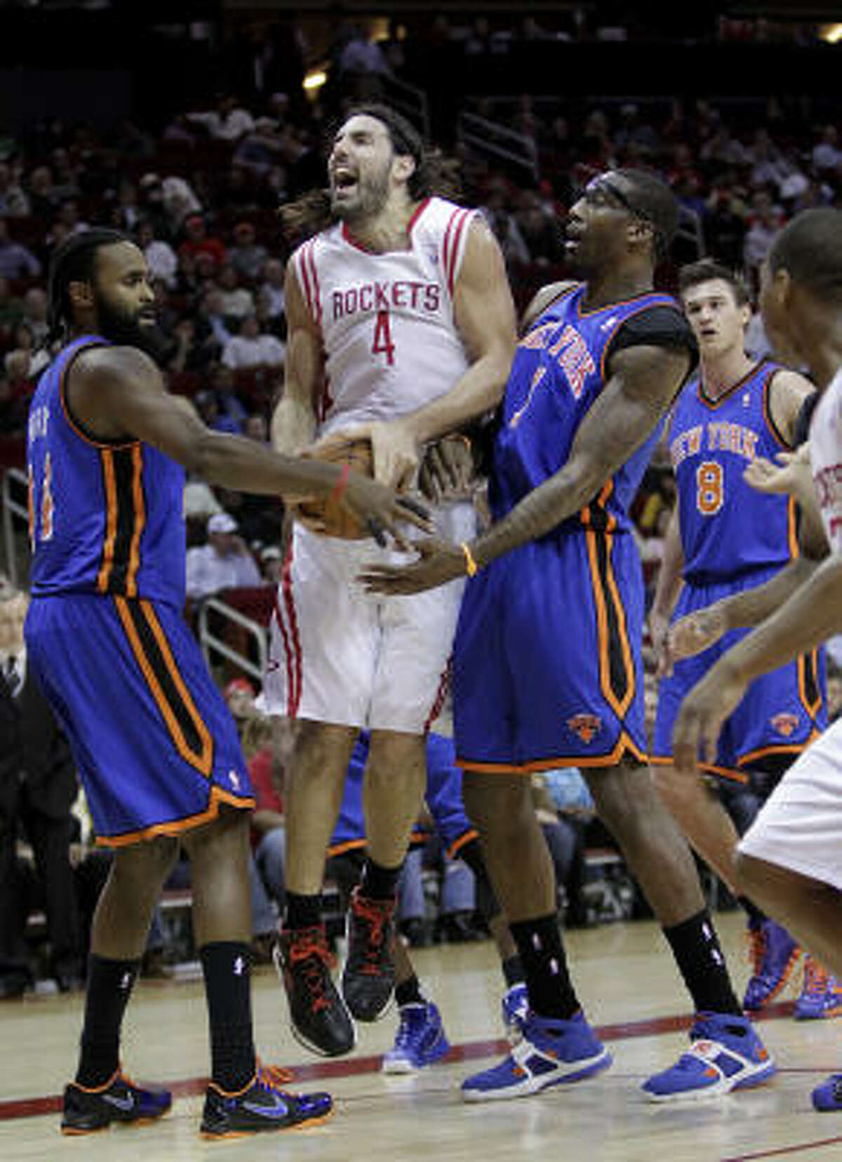 Rockets forward Luis Scola (4) is fouled by New York's Ronny Turiaf, left, and Amare Stoudemire during the first half.