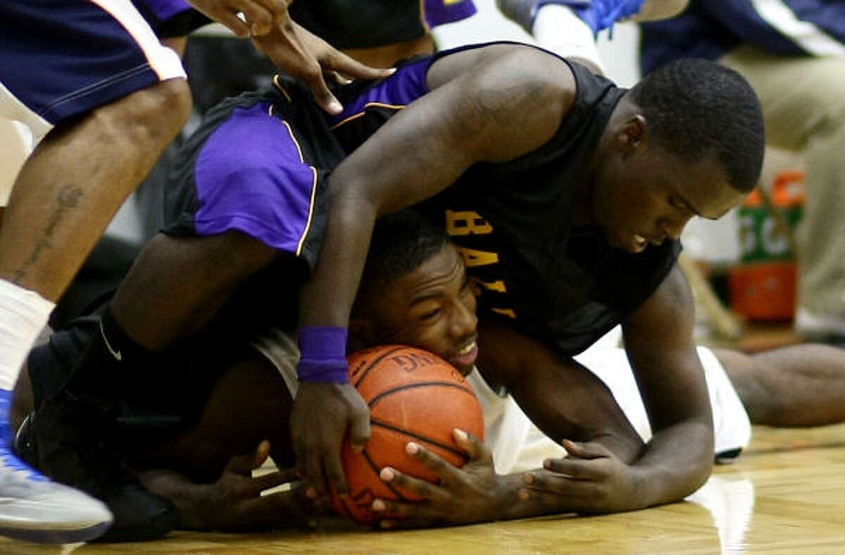 La Marque High School's Emmanuel Lewis, bottom, is squeezed by Ball High School's Josh Brown as they go for a loose ball.
