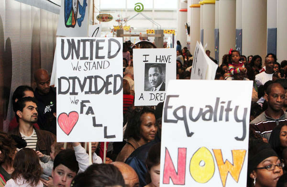 Visitors carrying signs during the MLK Day Peace Rally at the Children's Museum of Houston.