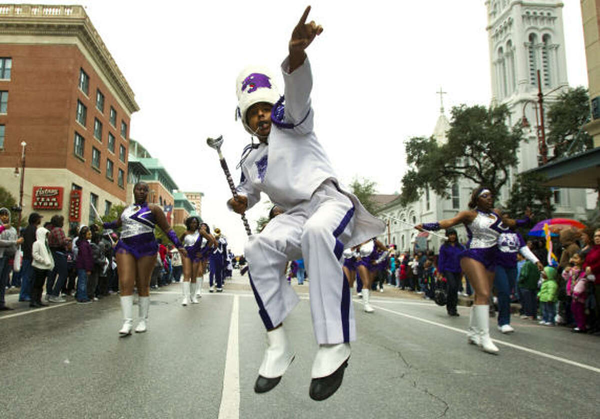 Drum Major Brandon Baylor jumps as he leads the Wheatley High School marching band during the Black Heritage Society's