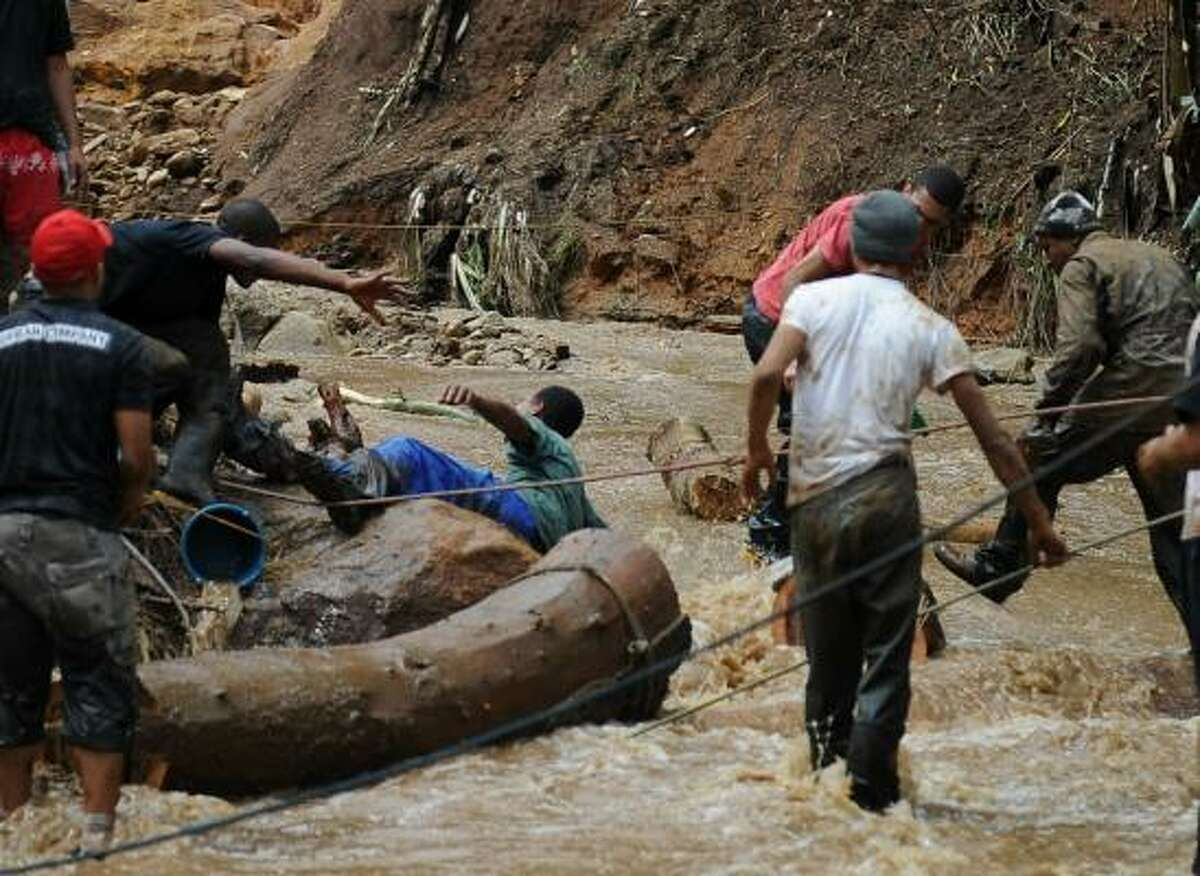 Rescuers hurry to help a man swept along by the waters in the fooded Kaleme neighborhood in Teresopolis, 100 km from downtown Rio de Janeiro, Brazil. Days of flooding and mudslides have left at least 109 people dead in southeast Brazil, with a mountainous region near Rio de Janeiro bearing the brunt.