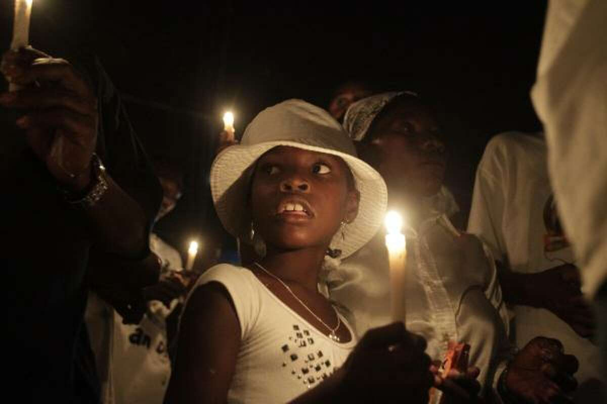 A group of Haitians mark the first anniversary of the magnitude-7.0 earthquake with a candlelight vigil and march in Port-au-Prince, Haiti. Wednesday marks the one-year anniversary that devastated the capital and is estimated to have killed more than 230,000 people and left millions homeless.