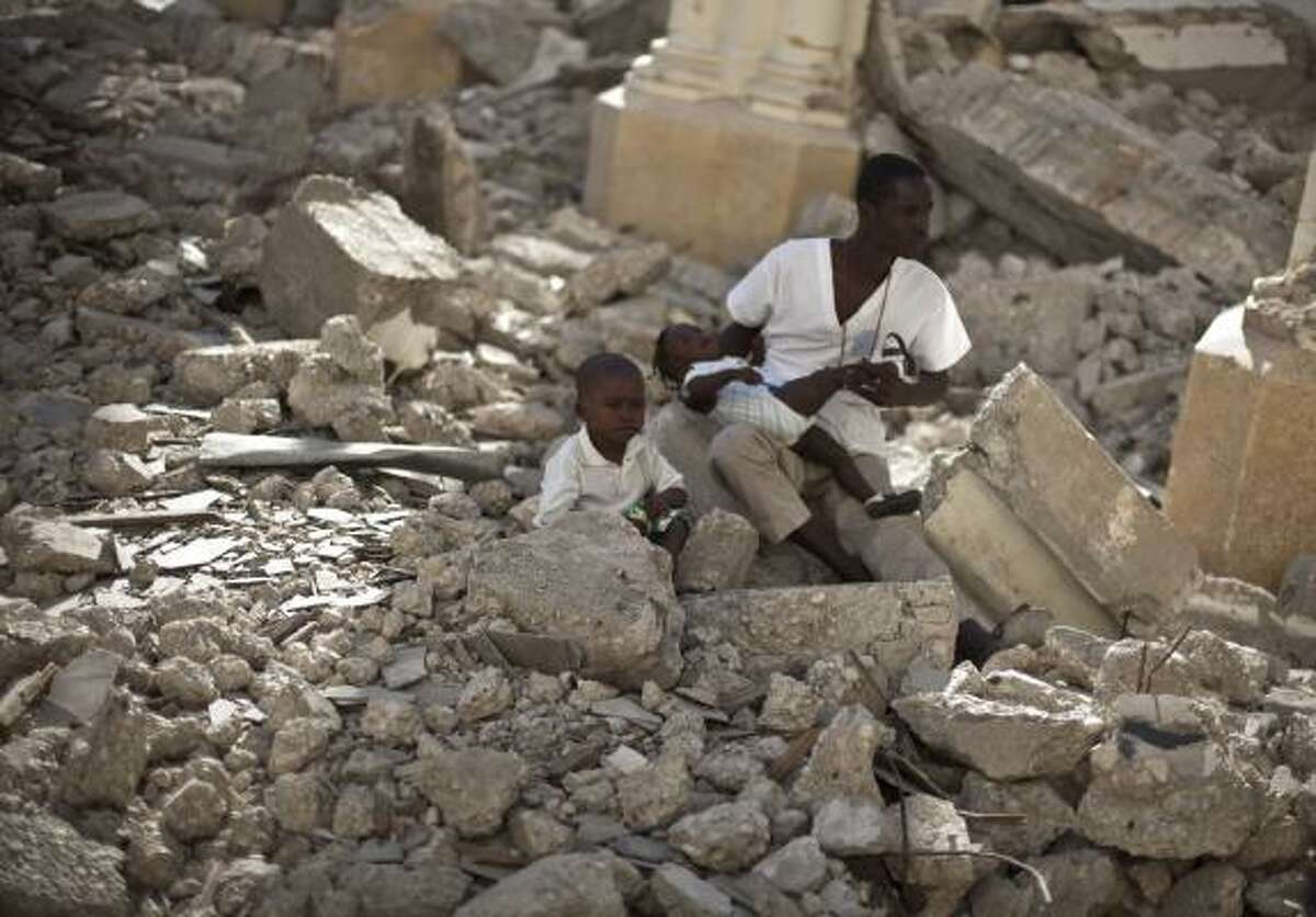 A man with two children sits in the rubble of the earthquake damaged Cathedral during a mass in Port-au-Prince, Haiti. Wednesday marks the one year anniversary since Haiti's magnitude-7.0 earthquake that devastated the capital and is estimated to have killed more than 230,000 people and left millions homeless.