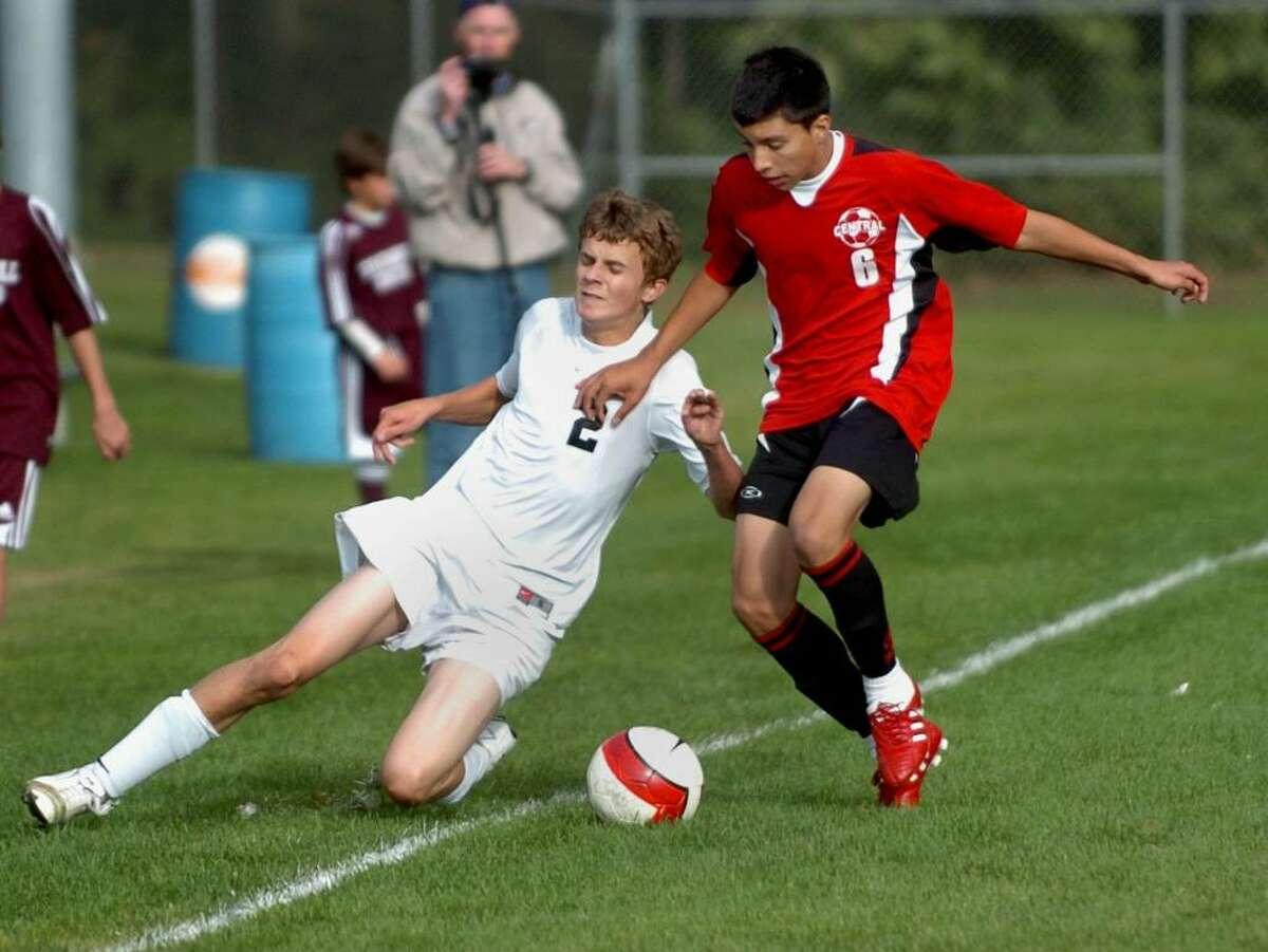 Trumbull's #2 Dan Helfrich, left, slides out of bounds as Central's #6 Harold Marin tries to keep the ball in play, during soccer action in Trumbull, Conn. on Thursday Oct. 01, 2009.