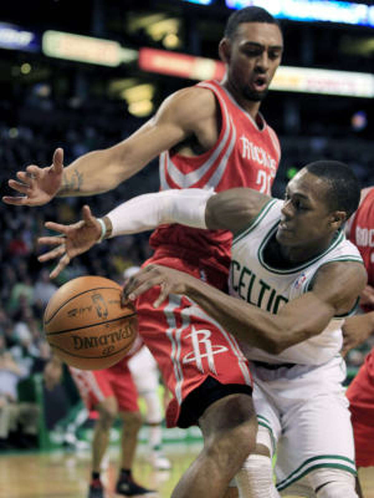Celtics guard Rajon Rondo, right, dumps the ball off as he is pressured by Rockets forward Jared Jefferies.