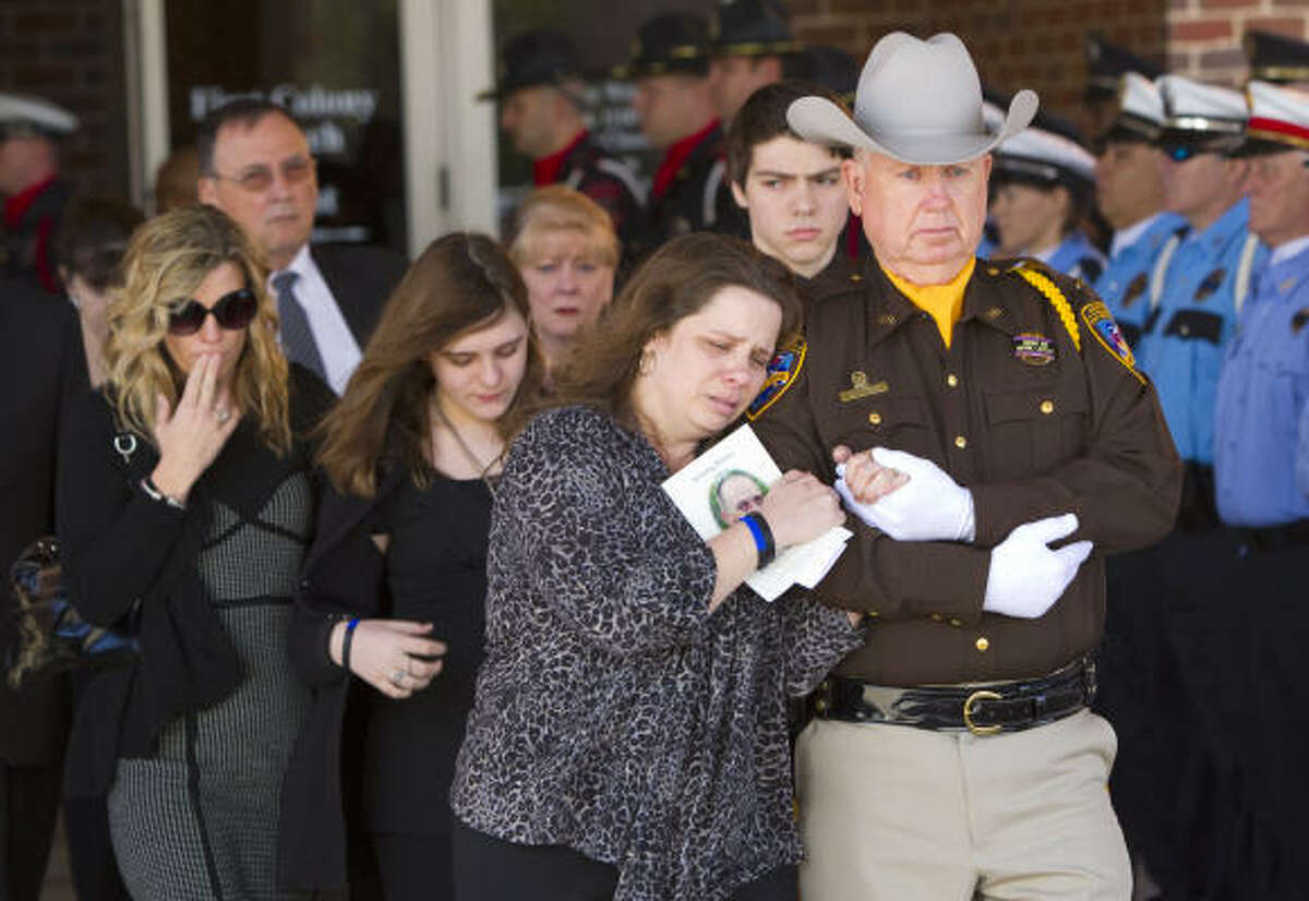 Lt. Sam Rader escorts Melissa Norsworthy from the First Colony Church of Christ following the funeral for her late husband, Fort Bend County Sheriff's Deputy John David Norsworthy, Jr. The deputy died Tuesday, a week after he crashed his squad car in the line of duty.