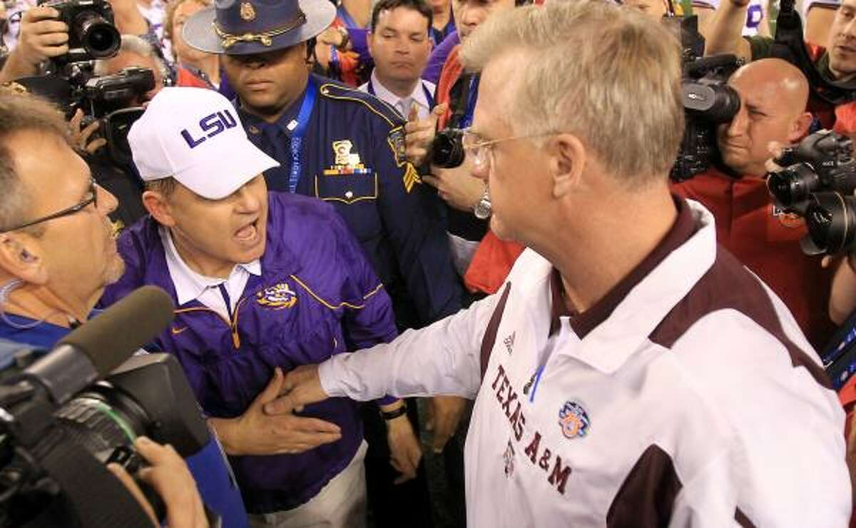 LSU head coach Les Miles, left, and Texas A&M head coach Mike Sherman shake hands at the end of the game.