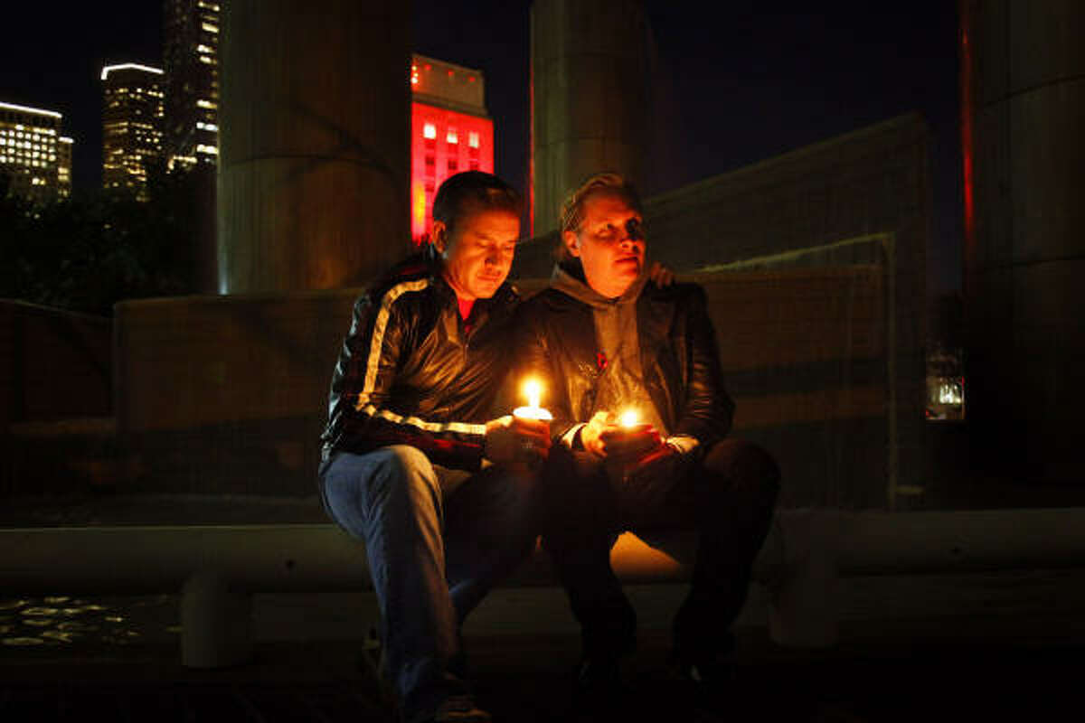 Victor Martinez and Barry Ouellette hold candles during the World AIDS Day Houston Candlelight Observance at Tranquility Park in Houston. Established in 1988, World AIDS Day is observed every December 1st as a day of hope, solidarity and understanding about the global epidemic HIV/AIDS.
