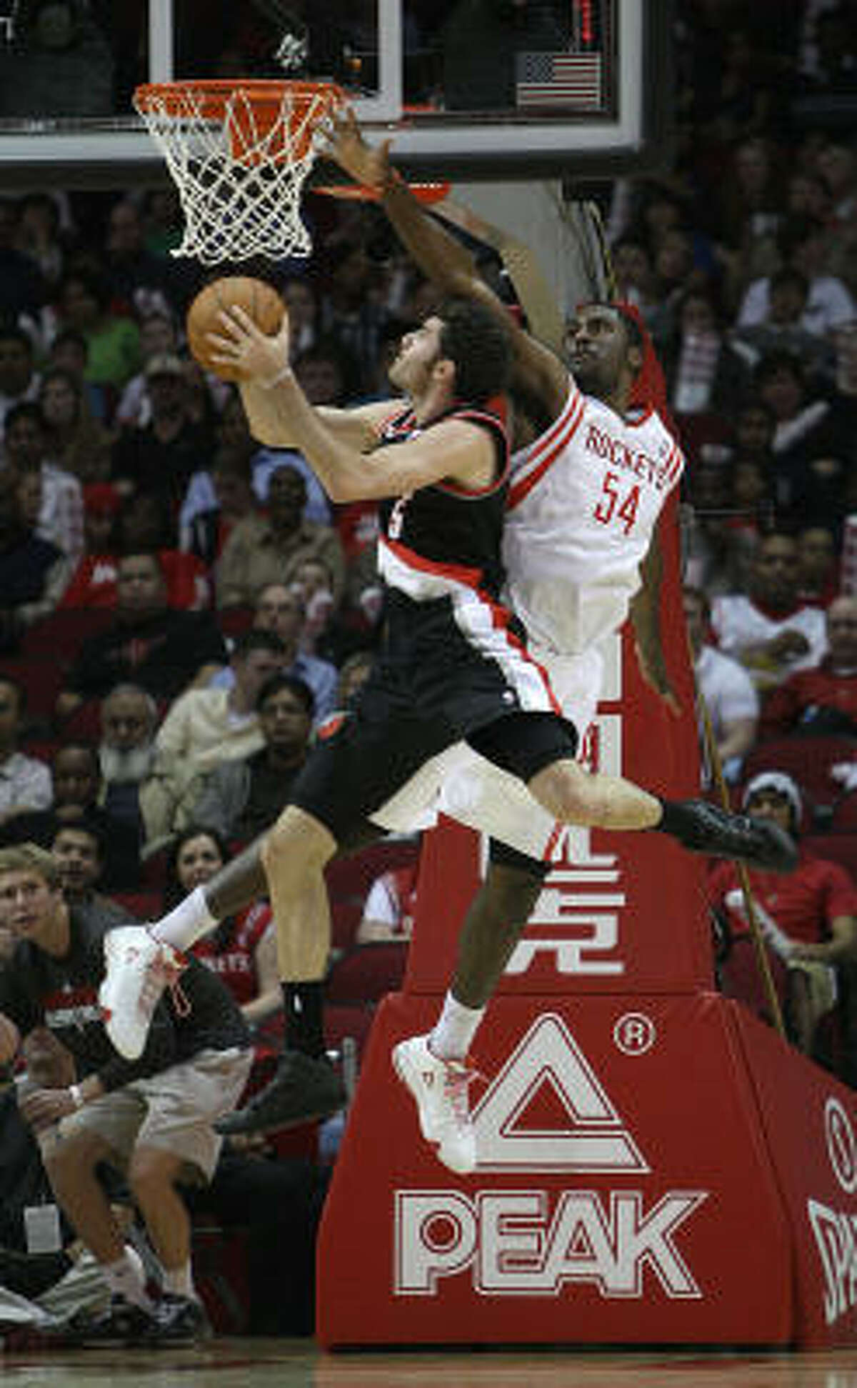 Rockets forward Patrick Patterson (54) tries to block a shot from Trail Blazers guard Rudy Fernandez during the first half.