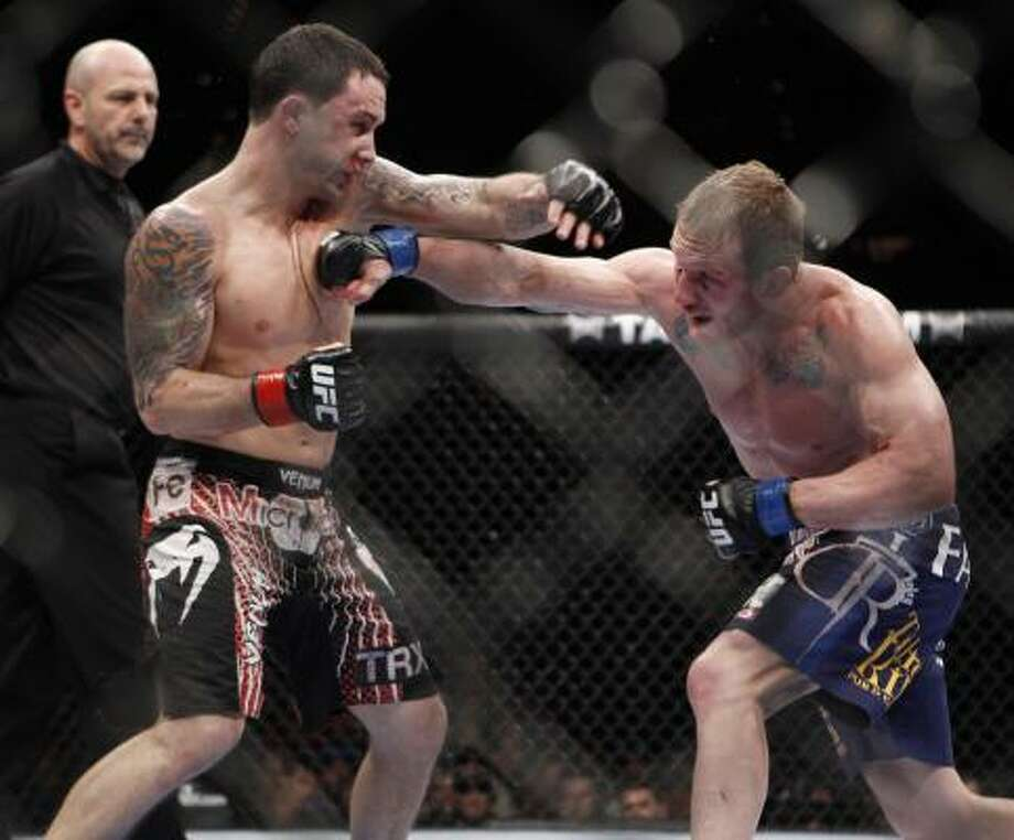 Frankie Edgar, left, trades punches with Gray Maynard during the fifth round of their UFC lightweight title match Saturday at the MGM Grand Garden Arena in Las Vegas. The fight was declared a draw, allowing Edgar to retain his title. Photo: Eric Jamison, AP