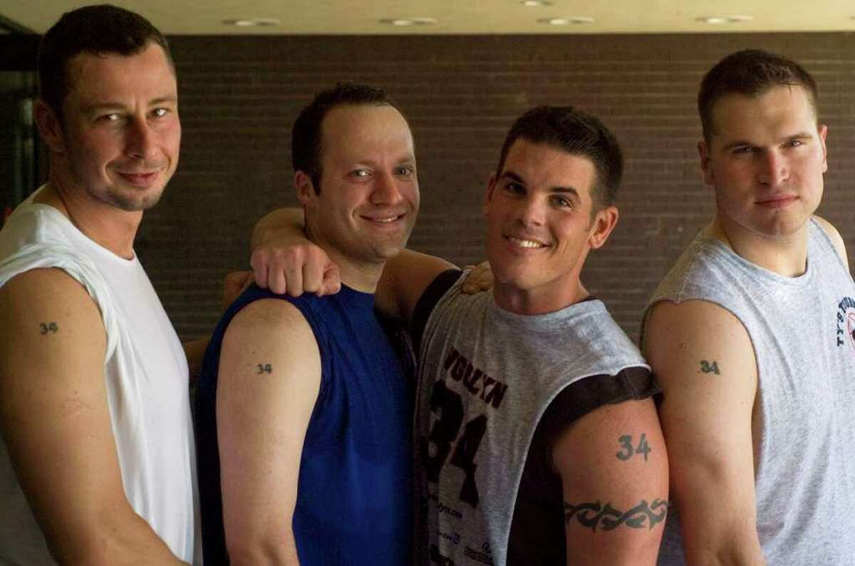 From left: Jon Krug, Andy Kirwan, Ron O'Brien and Jeff Elliott show off their number 34 tattoos during the Tyler Ugolyn Memorial Basketball Tournament at Ridgefield High School on Saturday, July 30, 2011. Tyler Ugolyn wore number 34 while at Ridgefield High School and at Columbia University. He was killed in the terrorist attacks on the World Trade Center on Sept. 11, 2001.