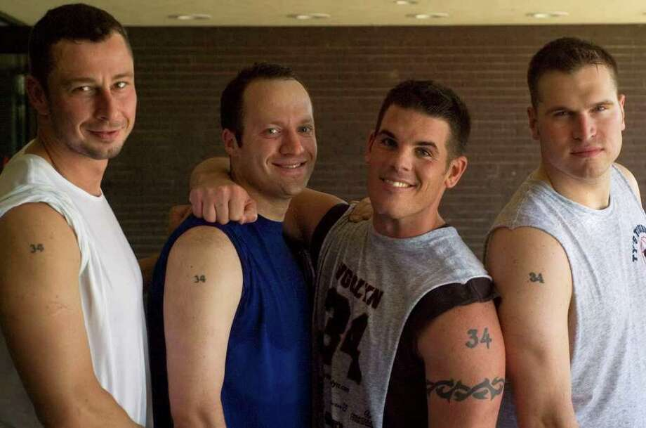 From left: Jon Krug, Andy Kirwan, Ron O'Brien and Jeff Elliott show off their number 34 tattoos during the Tyler Ugolyn Memorial Basketball Tournament at Ridgefield High School on Saturday, July 30, 2011.  Tyler Ugolyn wore number 34 while at Ridgefield High School and at Columbia University.  He was killed in the terrorist attacks on the World Trade Center on Sept. 11, 2001. Photo: Jason Rearick