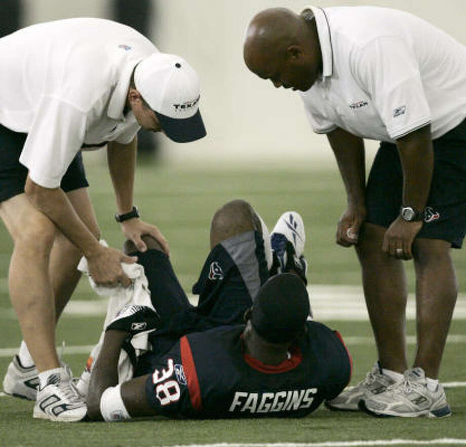 Houston Texans cornerback Demarcus Faggins points to his foot as he lies on the turf inside the Texans training bubble during Texans training camp on Friday. Faggins suffered a fractured foot that will require surgery and rehabilitation of six to 10 weeks. Photo: BRETT COOMER, CHRONICLE