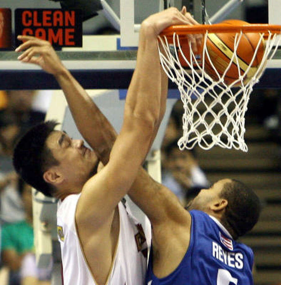 China's Yao Ming slam dunks the ball as Puerto Rico's Angelo Reyes tries to block him during their World Basketball Championship game. Photo: TOSHIFUMI KITAMURA, AFP/Getty Images