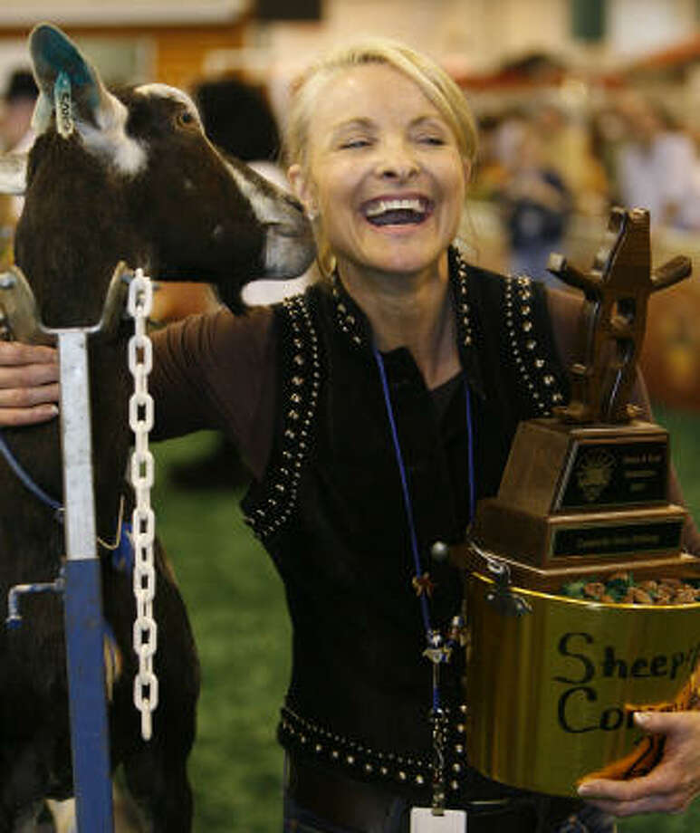 Dana Tyson, a host for the radio station 99.1, is kissed by a goat named Socks after winning  the Celebrity Goat Milking Contest during the Houston Livestock Show and Rodeo Friday. Photo: Melissa Phillip, Chronicle