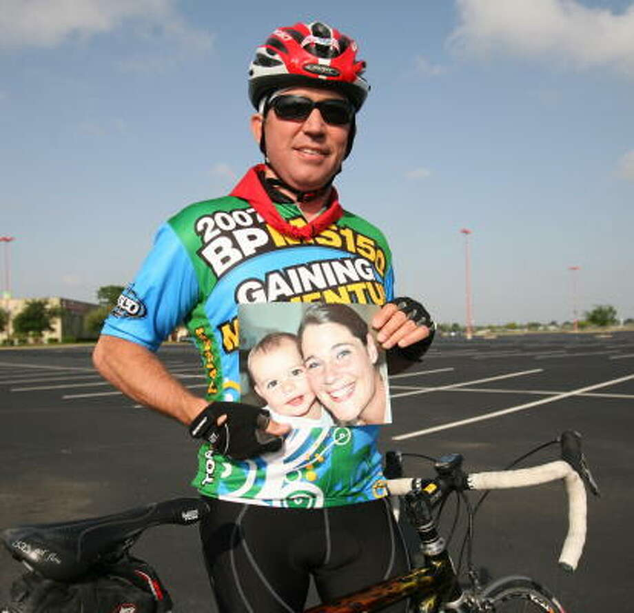 Evan Jones, 57, of Katy holds a photograph of his niece, Elisabeth, and her daughter, Grace, 2, of Seattle.   Jones will ride in the MS 150 bike race April 21-22 in honor of Elisabeth. Photo: Suzanne Rehak, For The Chronicle