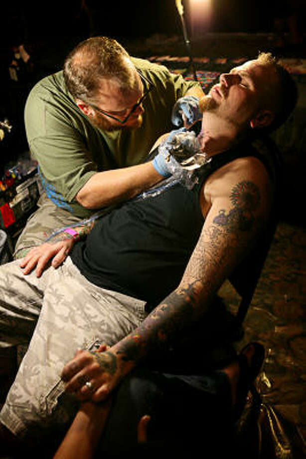 Brandon Davis, in the chair, holds the hand of his wife, Raquel Davis, while tattoo artist J.M.F.J. creates a tattoo on Davis' neck. Photo: ERIN TRIEB, FOR THE CHRONICLE