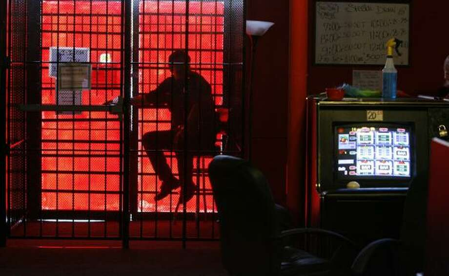 A security guard sits in a metal cage at a game room near Cavalcade and Jensen as police inspect the site. Photo: JAMES NIELSEN, CHRONICLE