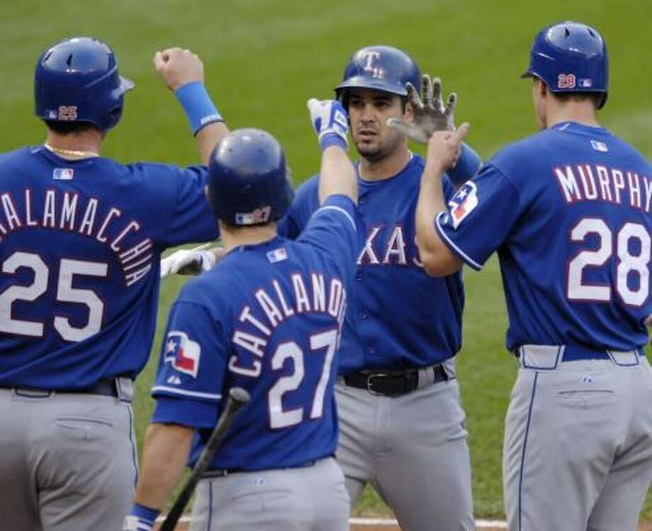 A Rangers traffic jam that wouldn't let up breaks out around home plate as Ramon Vazquez, second from right, celebrates his three-run homer in the fourth inning. Photo: NICK WASS, ASSOCIATED PRESS