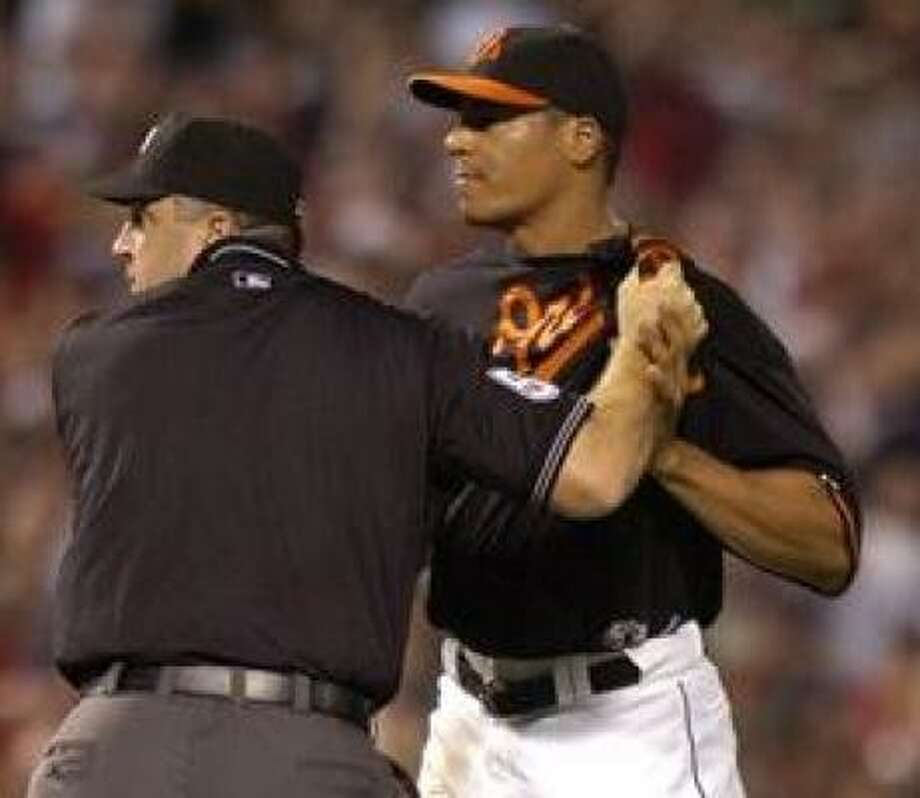 Baltimore Orioles pitcher Daniel Cabrera is held by umpire Bill Welke as the brawl begins in the fourth. Photo: Gail Burton, AP