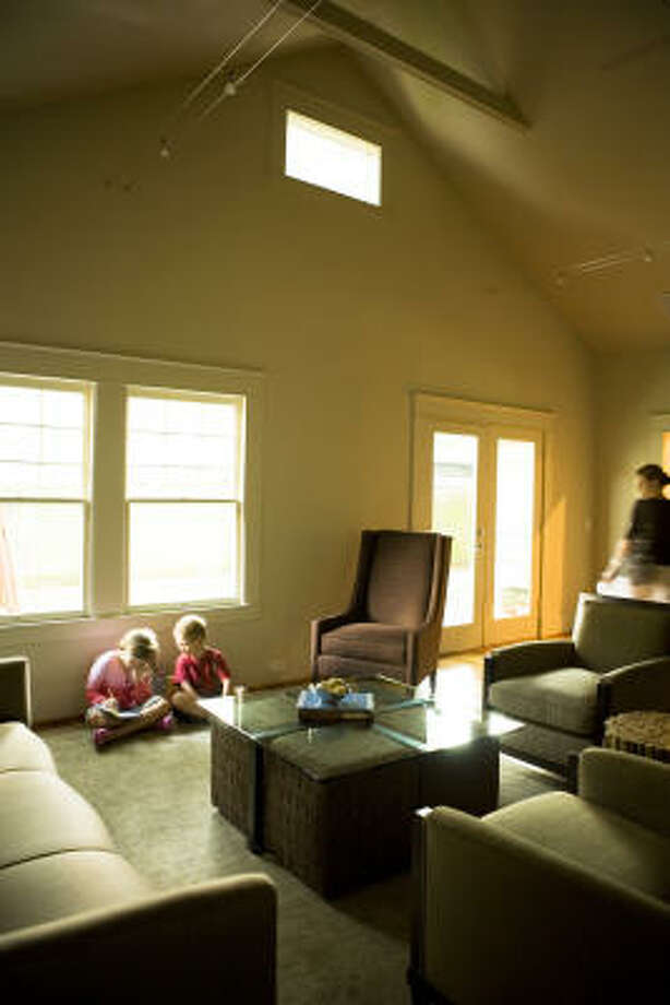 The children make themselves comfortable in the minimal family room - the heart of the home - as their mother looks on. Photo: Jill Hunter, For The Chronicle