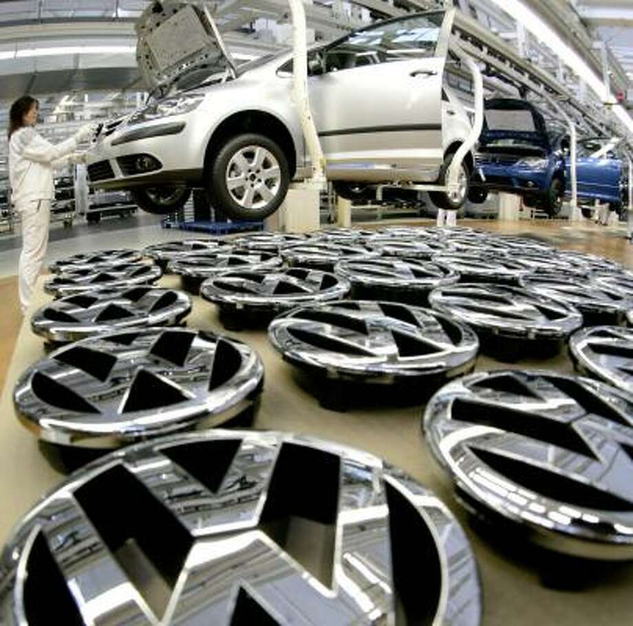 An assembly line worker attaches a VW logo to a Golf V in the company's Wolfsburg, Germany, plant. A ruling by the European Union's highest court will allow Porsche to make another bid for Volkswagen. Photo: KAI-UWE KNOTH, ASSOCIATED PRESS FILE