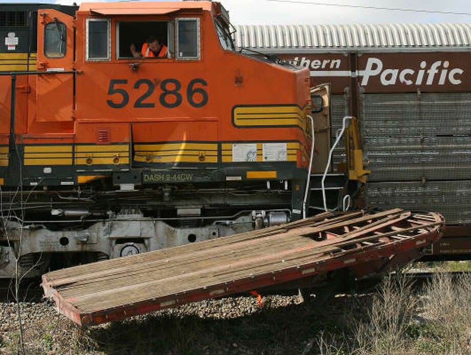 Railroad workers attempt to remove a flat bed trailer that got wrapped around the front of a train engine after a collision between the engine and the truck this morning. Photo: Billy Smith II, CHRONICLE