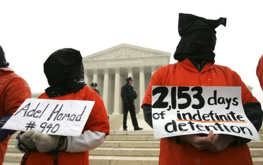 Demonstrators, some in prison-like orange jumpsuits, protest outside the Supreme Court Wednesday as it heard arguments about the rights of prisoners at Guantanamo Bay. Photo: LAWRENCE JACKSON, ASSOCIATED PRESS