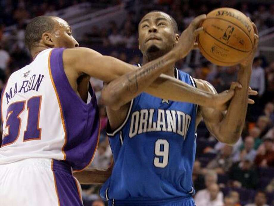 Phoenix's Shawn Marion, left, fouls Rashard Lewis in the first quarter Friday at Phoenix. The Suns won 110-106. Photo: PAUL CONNORS, ASSOCIATED PRESS